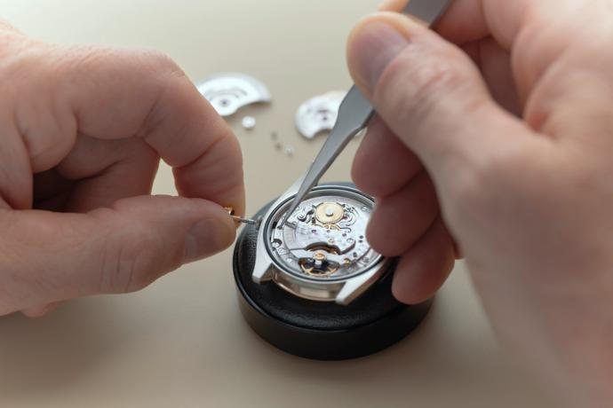 L'horloger enlève la tige de remontage afin d'extraire le mouvement du boîtier de la montre.