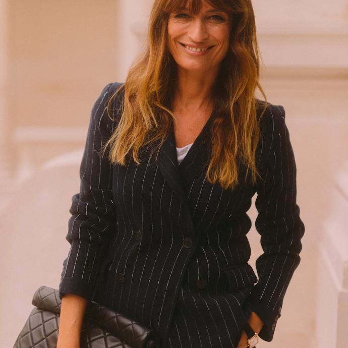 Caroline de Maigret portaitun jean gris de la collection Prêt-à-Porter Printemps-Eté 2021, une veste en cachemire Barrie et un sac Chanel.