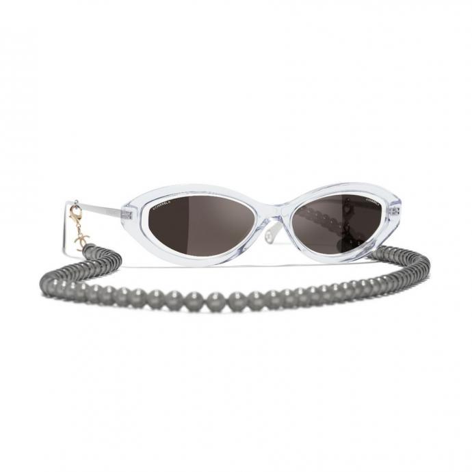 "Lunettes ovales, Chanel, 890 &euro;, <a href=""https://www.chanel.com/fr_BE/mode/p/sun/a71356x06086/a71356x06086s6057/lunettes-ovales-metal-acetate-resine-perles-de-verre-transparent.html"" target=""_blank"">disponible ici</a>."