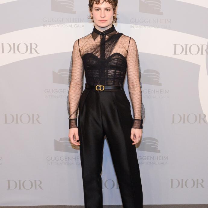 Christine and The Queens portait un ensemble Dior Haute Couture composé d'un pantalon et d'un bustier et chemise transparente, ainsi que de l'emblématique ceinture « CD » de la maison. Elle portait également des baskets Dior noires.