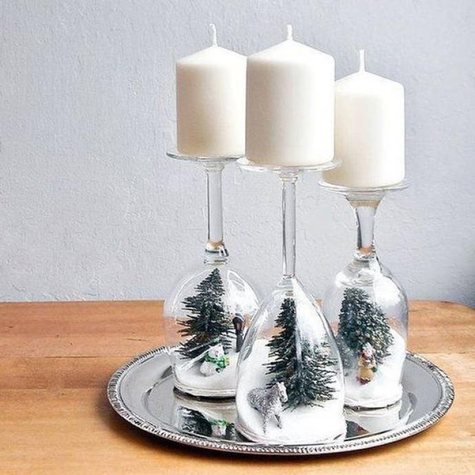 Quelques verres à pied, un peu de fausse neige et des petits sapins, il ne vous faudra rien de plus pour créer de jolis bougeoirs, à installer sur votre table de fête!