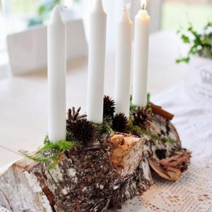 """Pour amener un peude nature """"brute"""", une sobre bûche percée de quelques trous dans lesquels insérer des longues bougies sera parfaite pour trôner au centre de votre table de Noël! Un peu de mousse et de pommes de pin (et d'autres choses encore) et l'affaire est dans la sac."""