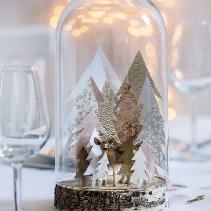 Du plus bel effet sur une table élégante et sobre, une haute cloche décorée de quelques sapins en papier et d'animaux hivernaux comme des rênes (ou des ours) créera une atmosphère enchantée sur votre table, avec en prime un joli jeu de transparence.