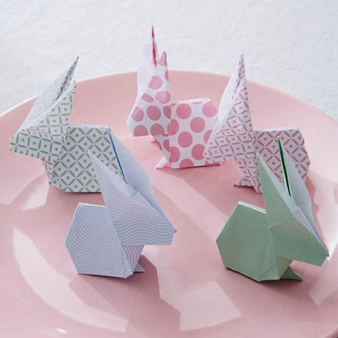 Ajoutez une touche d'originalité à votre table en créant des lapins en origami à déposer au centre de l'assiette de vos convives. Pour les réaliser, prenez des feuilles de papier à motif en forme de carré. Pour le pliage, suivez un tutoriel de manière à ne louper aucune étape.