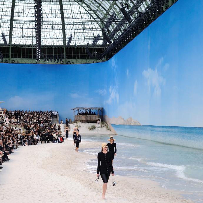 Karl Lagerfeld avait articulé une vraie plage de sable fin. Les mannequins, chaussures à la main, défilaient les pieds dans l'eau sous un « soleil » éclatant.