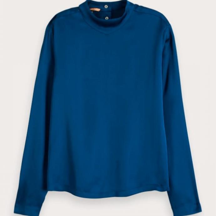 """Haut &agrave; col montant en satin bleu, Scotch&amp;Soda, 99,95 euros. Shoppez-le <a href=""""https://www.scotch-soda.com/be/fr/femme/chemisiers-et-blouses/haut-a-col-montant-en-satin/154114.html?cgid=25&amp;dwvar_154114_color=Sapphire%20Blue#position=2"""" target=""""_blank"""">ici</a>.&nbsp;"""