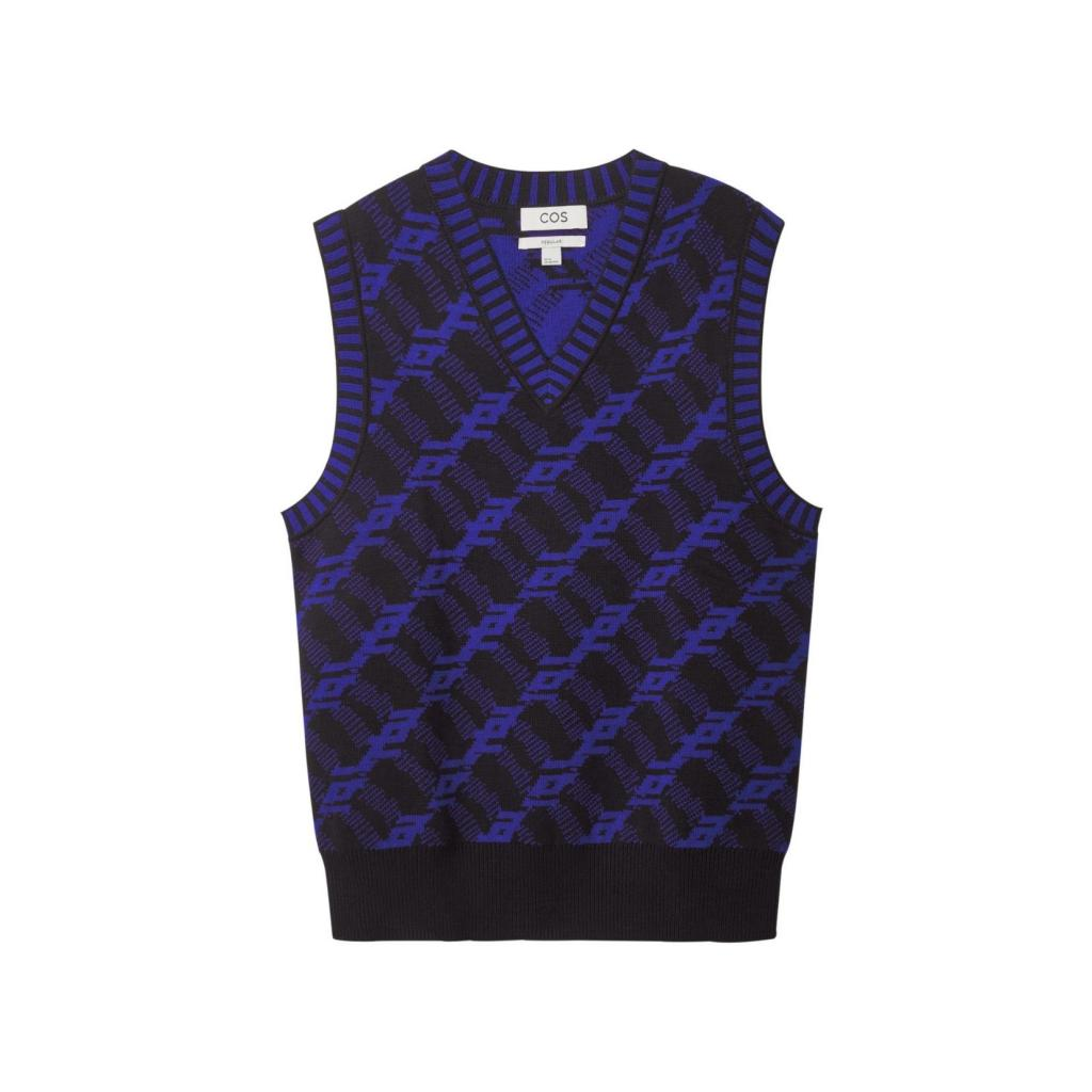 """Debardeur pour hommes a chevrons bleu et noir, COS, 59 €, <a href=""""https://www.cosstores.com/en_eur/men/menswear/tops/product.regular-fit-jacquard-vest-blue.1011241001.html"""" target=""""_blank"""">à shopper ici.</a>"""