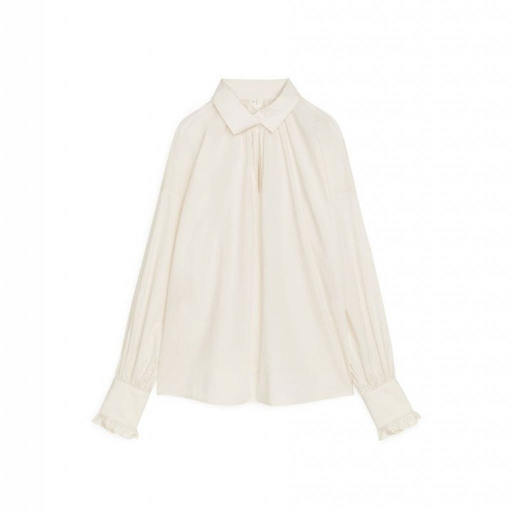 """Chemise blanc cassé, Arket, 79 €, disponible <a href=""""https://www.arket.com/en_eur/women/shirts-blouses/product.gathered-poplin-blouse-white.0929497003.html"""" target=""""_blank"""">ici.</a>"""