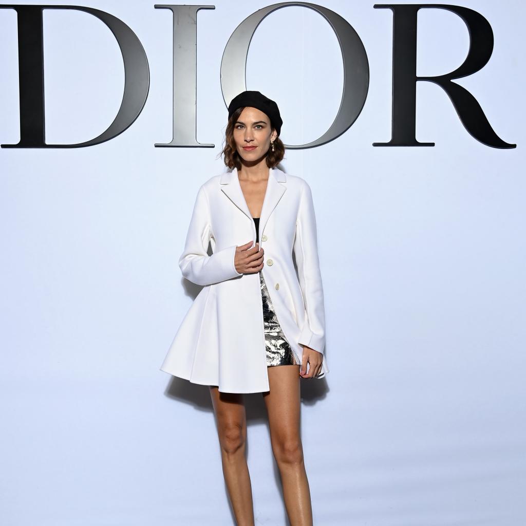 La mannequin anglaise Alexa Chung portait une veste en cachemire blanche, une brassière en tricot noir et une jupe métallique argentéDior.