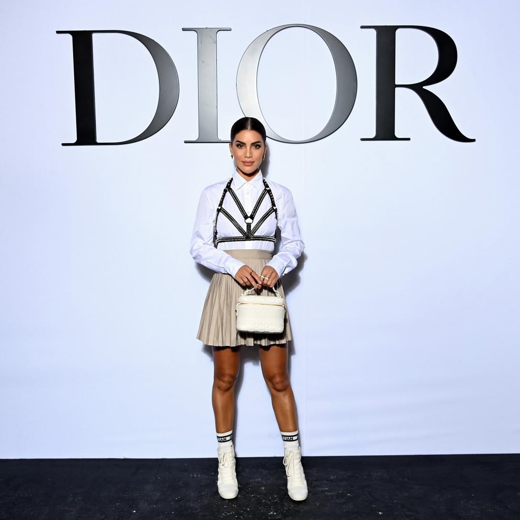 Camila Coelho portait une jupe plissée sur une chemise blanche surmontée d'un bustier harnais Dior.
