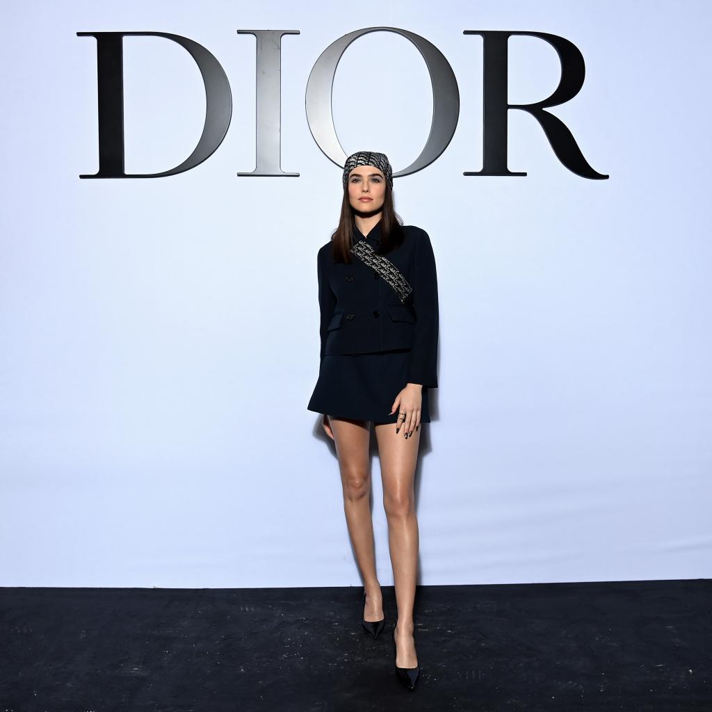 Zoey Deutch portait une veste et une jupe en laine et soie bleu marine Dior Cruise 2022, un foulard en soie bleu Dior, un sac Saddle bleu Dior et des chaussures Dior.