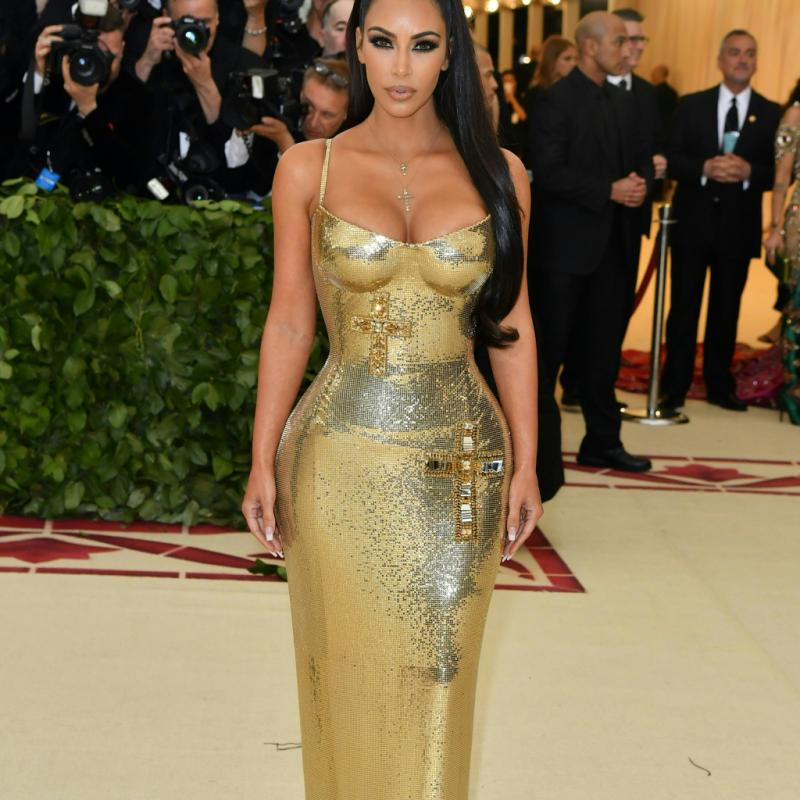 Sculpturale, Kim Kardashian a foulé le tapis rouge dans une robe moulante or métallisé signée Atelier Versace. Le tout accessoirisé avec un collier doté d'un pendentif en forme de croix. New York, le 7 mai 2018. © Hector RETAMAL / AFP