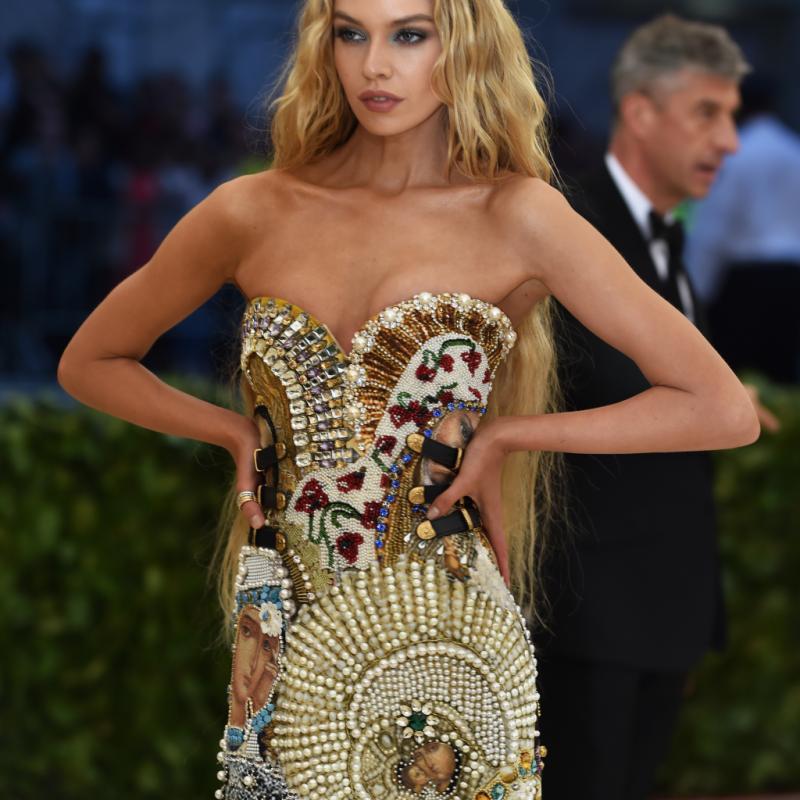 Angélique, Stella Maxwell portait une robe Moschino entièrement brodée de perles, de pierres, et de peintures représentant des symboles religieux. New York, le 7 mai 2018. © Hector RETAMAL / AFP