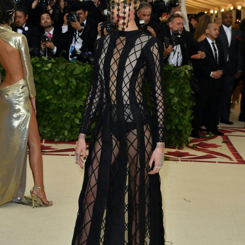 Si Cara Delevingne a opté pour une tenue sombre, semi-transparente, signée Dior, elle a en revanche choisi un make-up couleur or, visible derrière un masque d'un nouveau genre. New York, le 7 mai 2018. © Hector RETAMAL / AFP