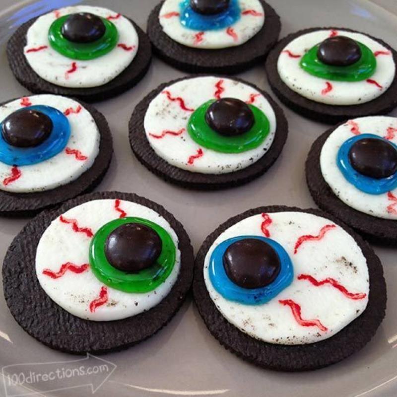 """<strong>Ingr&eacute;dients </strong>: des biscuits type or&eacute;o,gel en tube sp&eacute;cial p&acirc;tisserie ( vert ou bleu), gel colorant alimentaire rouge, des smarties noir, un pinceau fin. <em>Retrouvez la recette compl&egrave;te <a href=""""https://www.trucsetbricolages.com/cuisine/des-yeux-pour-collation-un-biscuit-transforme-pour-amuser-les-enfants-a-l-halloween"""">ici</a>.</em>"""