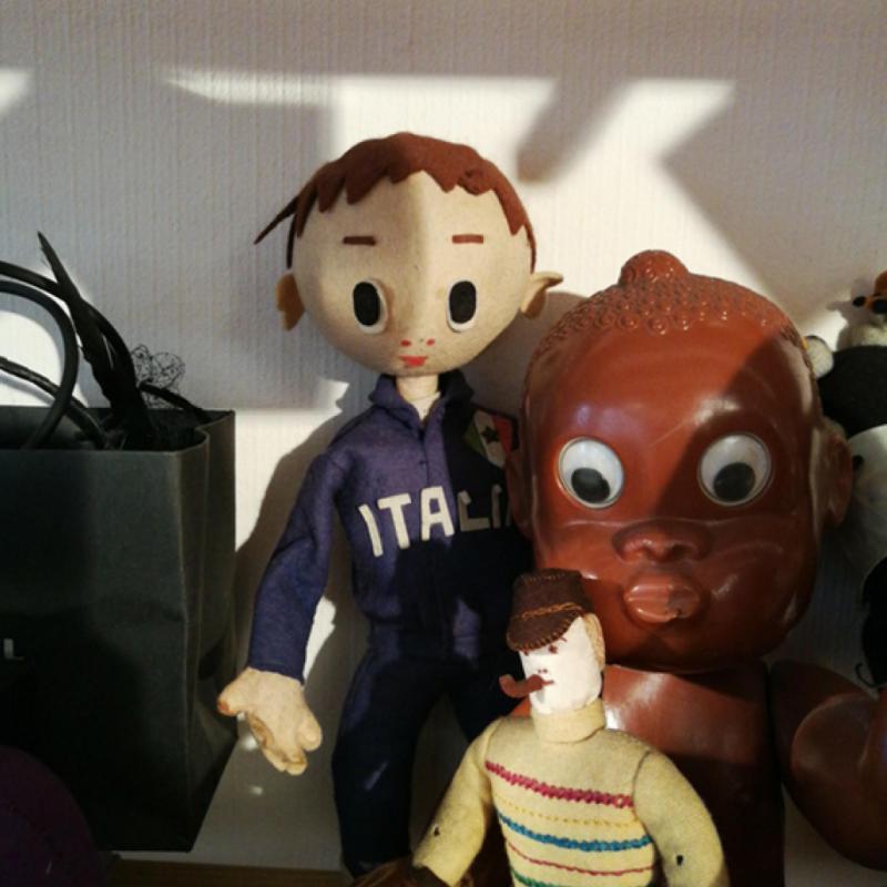 Un ensemble de poupées anciennes, dont un petit pompiste italien au regard malicieux.