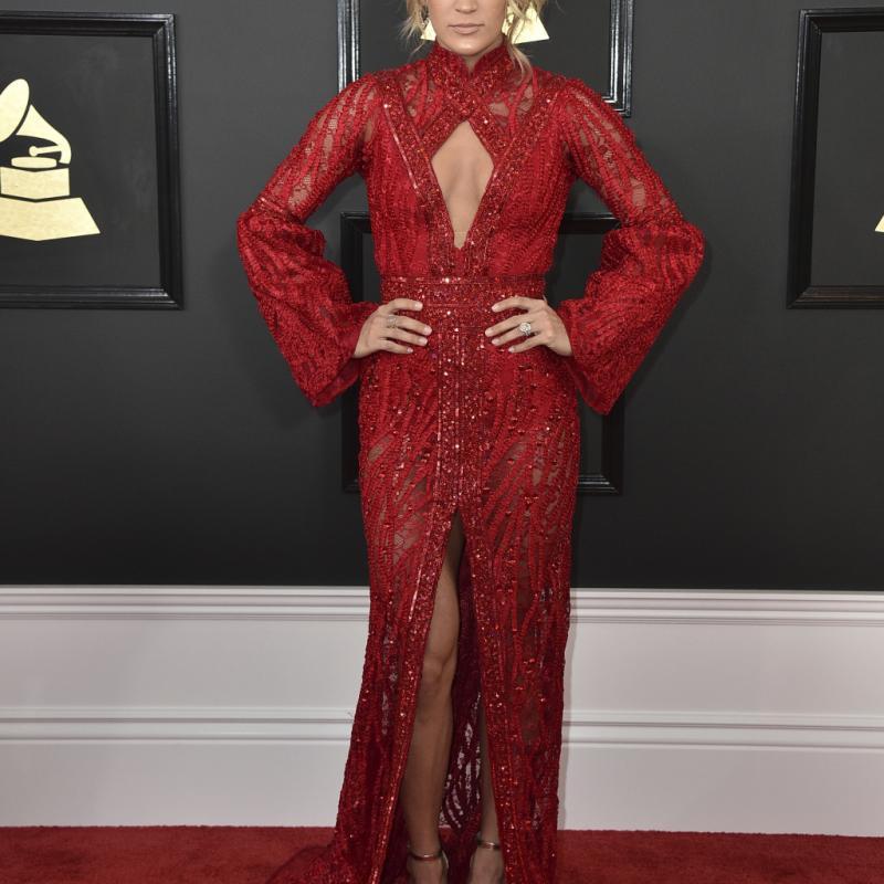 La classe de Carrie Underwood dans cette longue robe rouge Yas Couture est incontestable. Décolleté goutte, effets de manches et de transparence, pour un look chic, so red carpet.