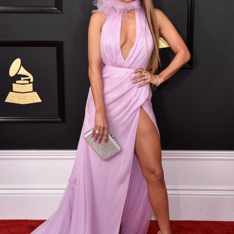 Jennifer Lopez dévoile sa silhouette et son teint mat avec une robe longue lavande fendue Ralph & Russo. Le plus ? La grosse fleur en tulle nouée autour de son cou.