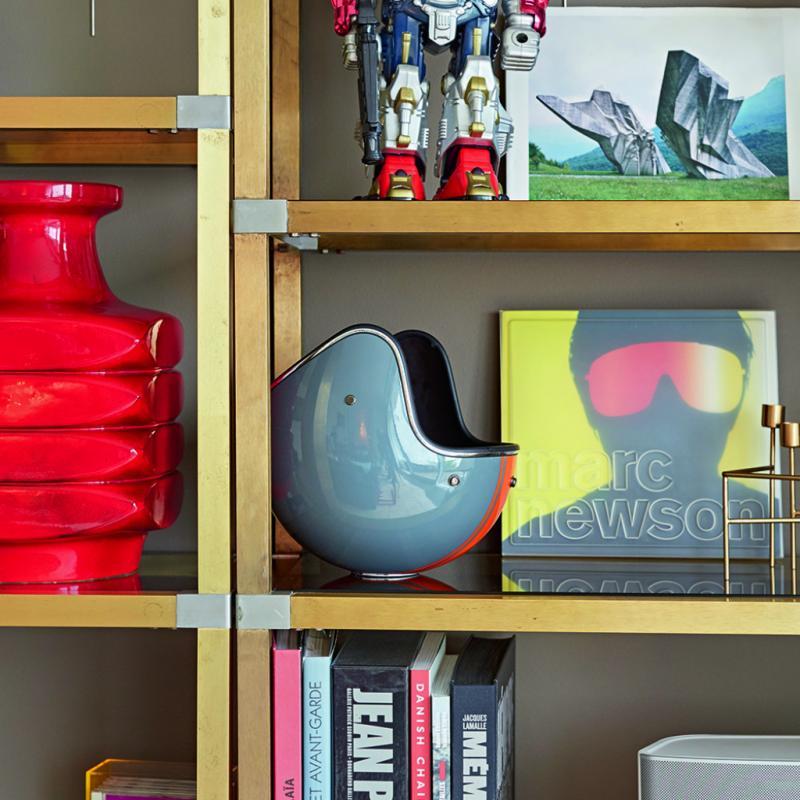 La bibliothèque est un joyeux bric-à-brac d'objets de différentes époques, ludiques et colorés. Je les aime tous, le robot, le casque (qui est en fait un seau à champagne) et ce magnifique vase rouge de chez Patterns. C'est le premier objet moderne que mon mari a apprécié, lui qui n'aime que l'esthétique du XVIIIe siècle. Je ne pouvais pas ne pas le mettre en évidence chez nous! Et puis il y a les livres; c'est un élément essentiel pour moi. Je les déplace, je les consulte, ils ne sont pas du tout là uniquement pour faire joli.