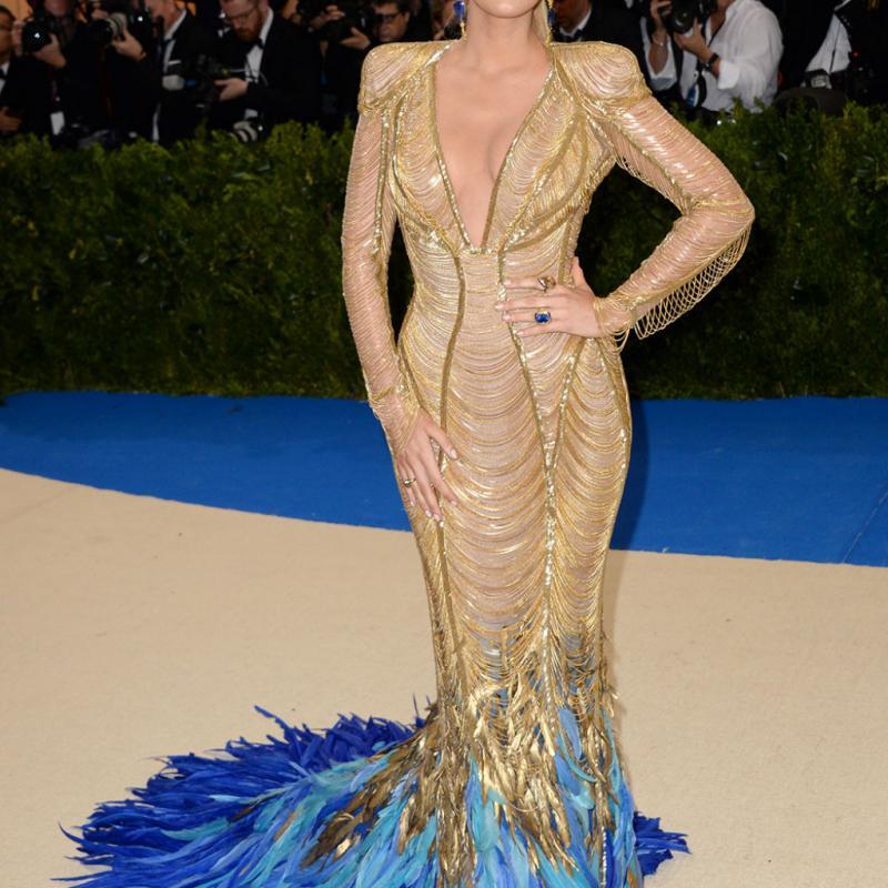 Blake Lively - Atelier Versace Une fois n'est pas coutume, l'actrice de « Gossip Girl » a illuminé les marches du Met Gala avec sa robe sirène dorée signée Versace, pourvue d'un magnifique décolleté plongeant et d'une traîne de plumes bleues.