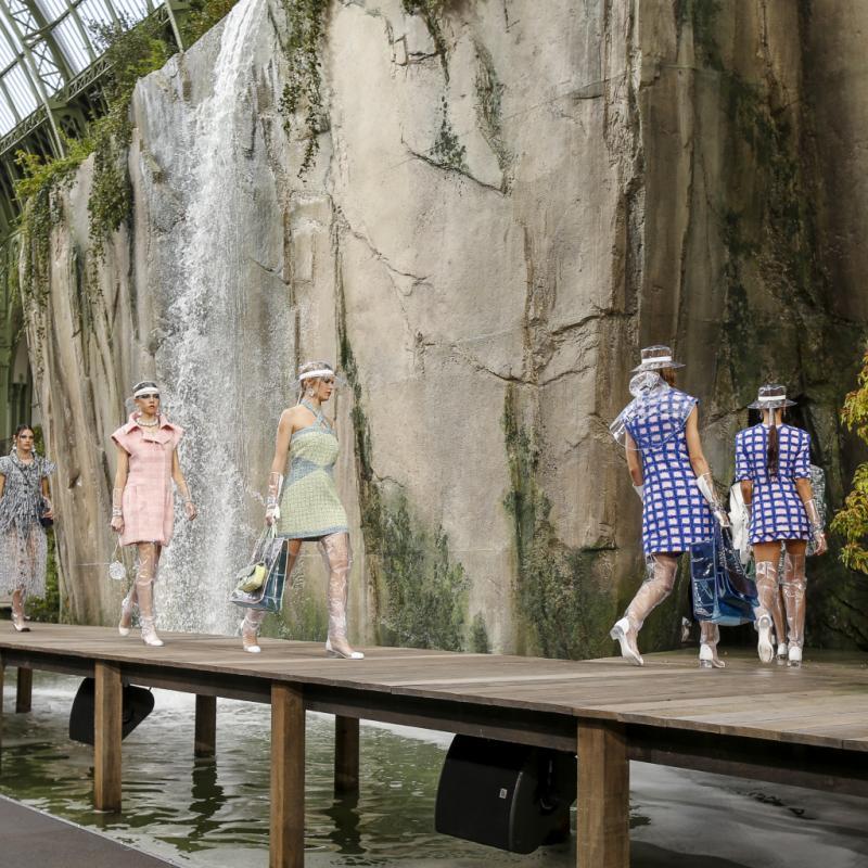 Un décor naturel composé d'une cascade de plusieurs mètres, de murs en pierre, d'arbres verdoyants et d'un pont en bois faisant office de podium.