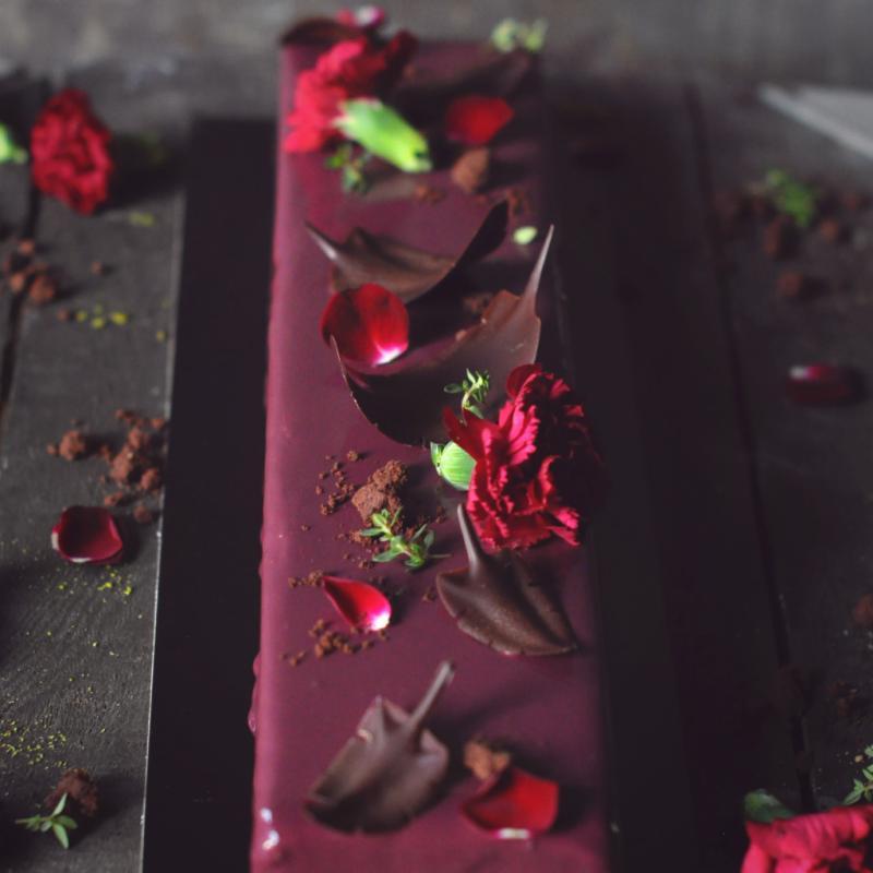Combinaison d'une mousse au chocolat noir, avec un coeur composé d'une crème brûlée à la vanille et d'une compotée de cassis légèrement parfumé à la violette, un crumble cacao à la fleur de sel (SANS GLUTEN). Prix: 6€/personne (disponible en 4,6 ou 10 personnes).
