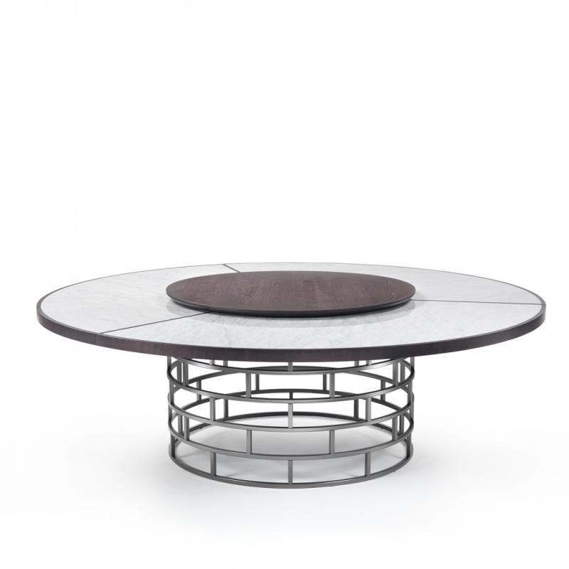 Une table ronde dessinée par Roberto Lazzeronni qui s'articule autour d'une structure grille en métal cylindrique, une couronne sur laquelle repose un plateau en bois massif incrusté de trois pièces de marbre. Avec ses 240 cm de diamètre, elle offre élégance et aisance aux convives qui s'y attableront…