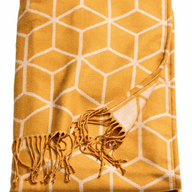"""Plaid en tissu jacquard (130 x 170cm), 29,99€. H & M Home. <a href=""""http://www.hm.com/home"""">www.hm.com/home</a>."""
