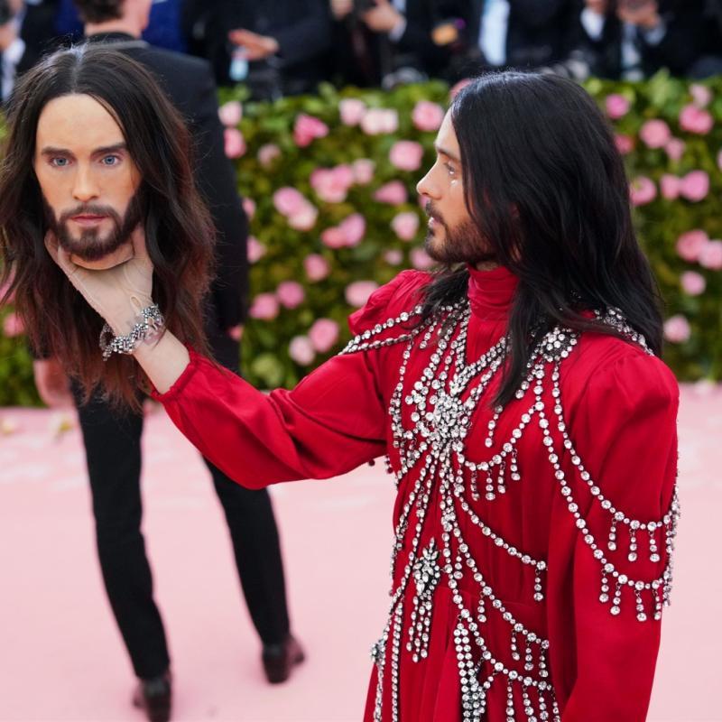 Vêtu de Gucci, l'acteur Jared Leto portait une robe à col haut avec des épaulettes et incrustée de bijoux. Mais c'est surtout son accessoire qui aura le plus marqué les esprits : une reproduction de tête humaine à son effigie