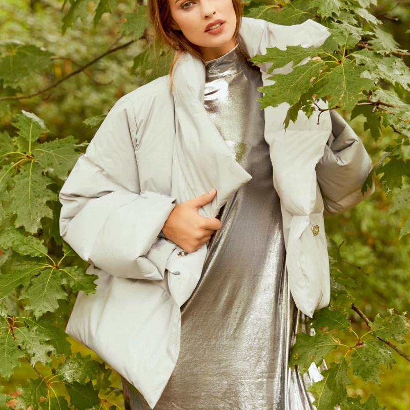 Indispensable de l'hiver, on la choisit oversized, en version édredon pour un style affuté. Doudoune courte gris Perle, COS, 175€. Robe métallique asymétrique, Weekday, 40€.